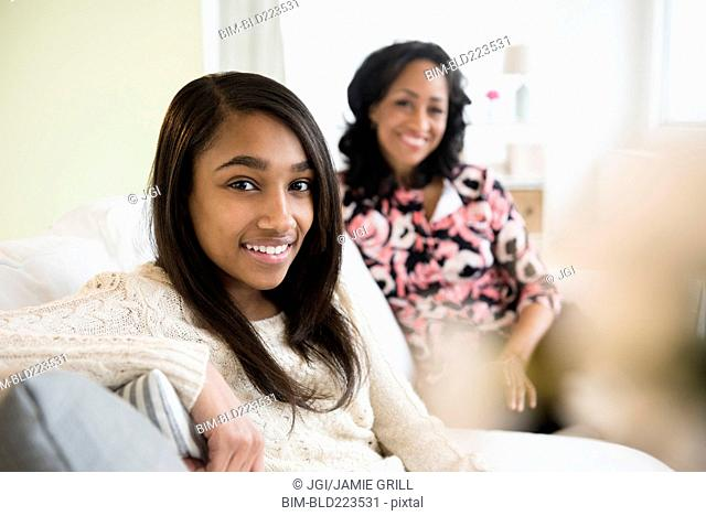 Smiling mother and daughter sitting on sofa
