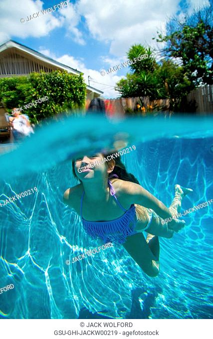 Young Girl Swimming underwater in Swimming Pool