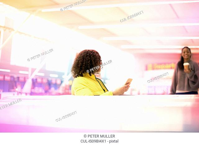 Two mid adult women meeting in airport departure lounge