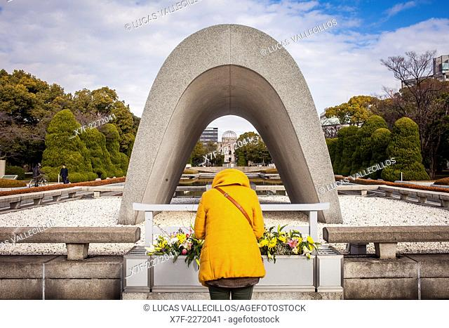 Praying, Cenotaph for the Atomic bomb victims, in background Atomic Bomb Dome, Peace Park, Hiroshima, Japan