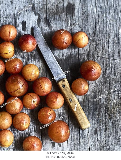 Wild plums (ringlovs) with a knife on a wooden surface