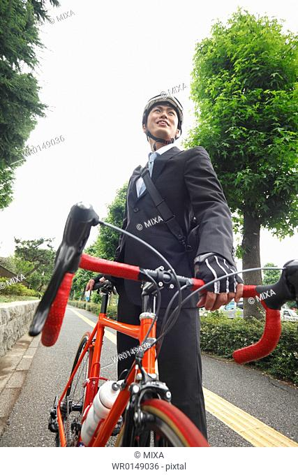 Young businessman holding bicycle