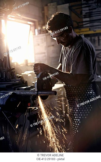 Blacksmith using saw in forge