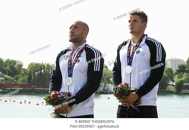 Germany's Ronald Rauhe (L) and Tom Liebscher attend the medal ceremony after coming second in the Men's Kayak Double K2 200m final at the 2015 European Games