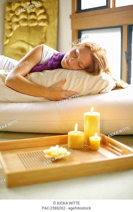 A woman sleeping on a bed with candles burning on a table; Hawaii, United States of America