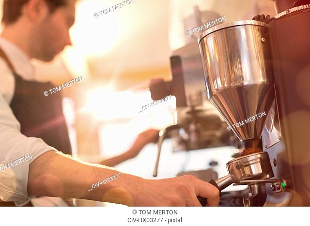 Barista using espresso machine grinder in cafe