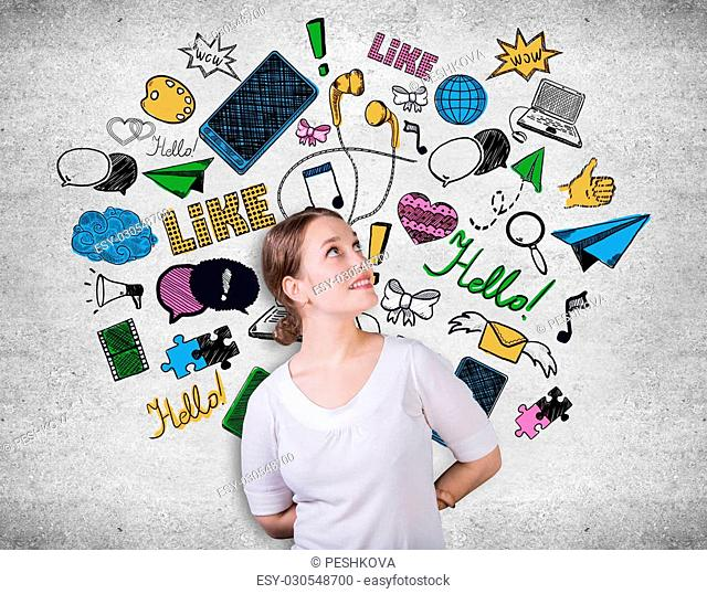 Attractive young woman on concrete background with creative communication icons drawings. Social media concept