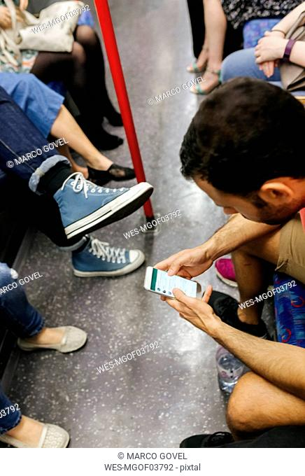 UK, London, man in underground train looking at cell phone