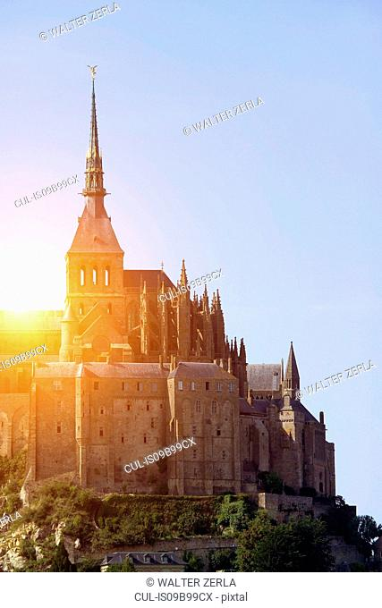 Sunlit view of Mont Saint-Michel against blue sky, Normandy, France