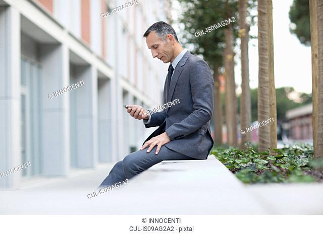 Businessman on lunch break texting on smartphone