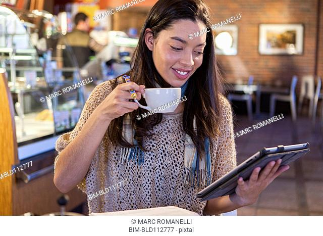 Mixed race woman using tablet computer in coffee shop