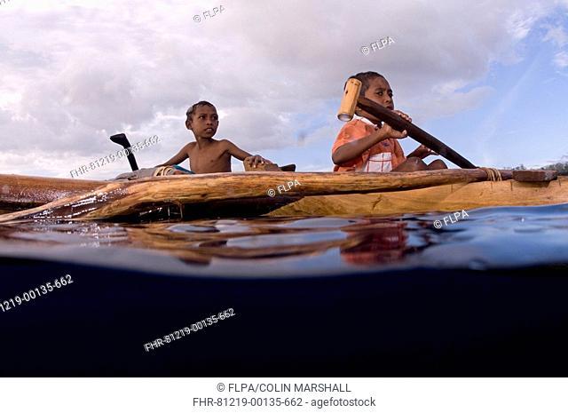 Boys rowing canoe at sea, near Perai Village, West Wetar Island, Alor Archipelago, Lesser Sunda Islands, Indonesia