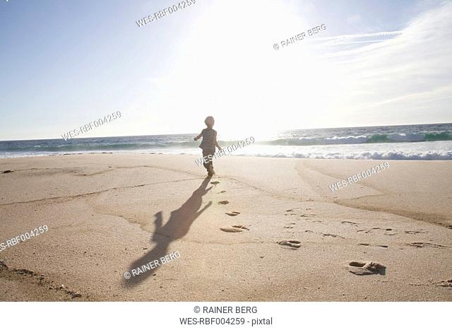 Back view of boy running on the beach at twilight