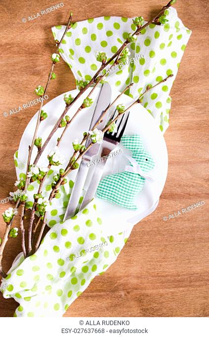 Festive table setting for Easter dinner with spring flowers and cutlery on wooden rustic table. Selective Focus