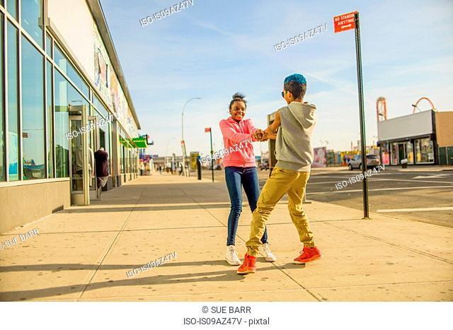 Teenage boy and girl holding hands and spinning each other around on sidewalk, Brooklyn, USA