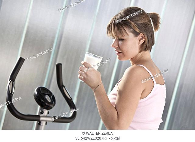 Woman drinking milk in home gym