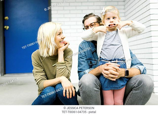 Girl making a face with her parents