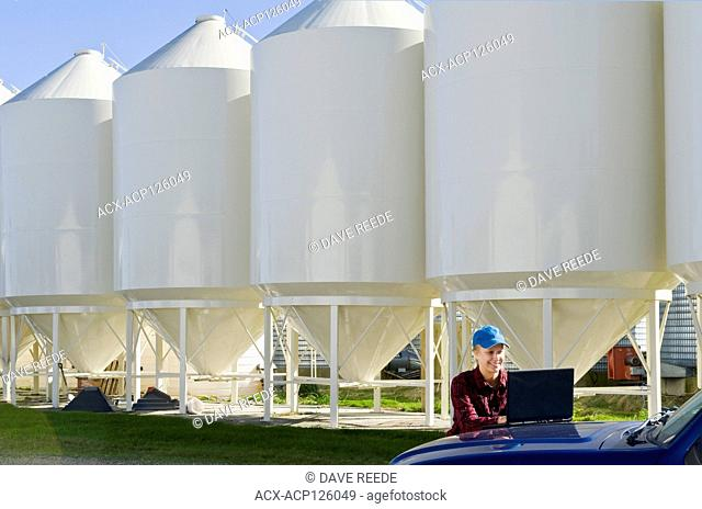 girl using a computer next to seed storage hopper bins in a farmyard, near Dugald, Manitoba