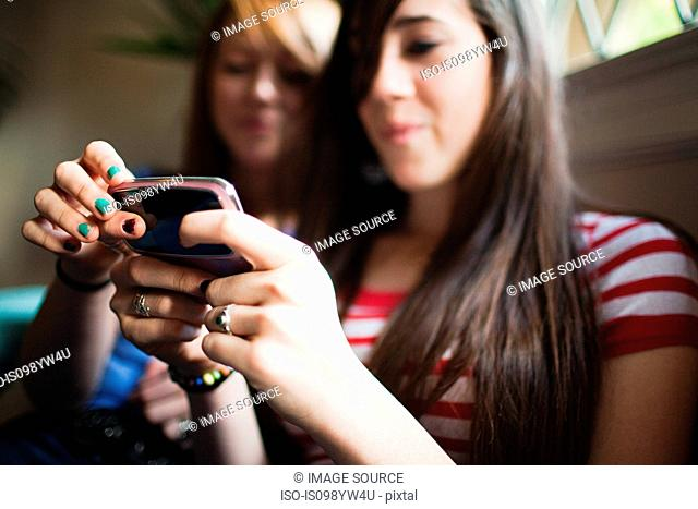 Two teenage girls using smartphone