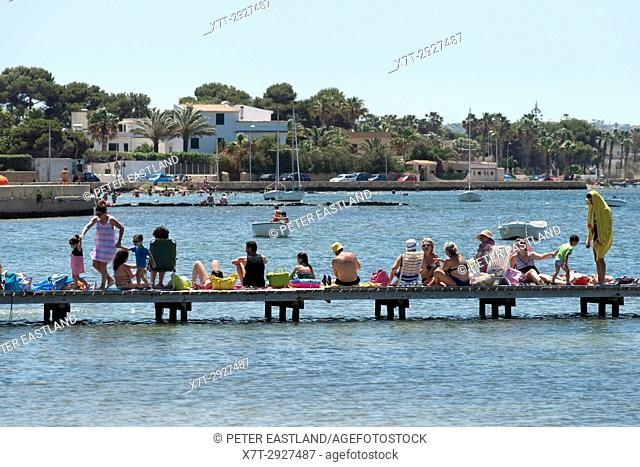 Holiday makers sunbathing on a pontoon at Marsala in Western Sicily, Italy