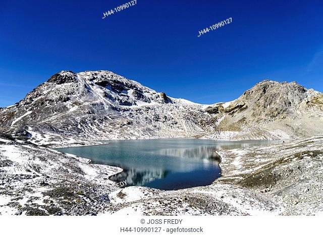 The mountain lake Lajet da Lischana near the valley Val S-charl, Lower Engadine, Switzerland. In the background the mountains Piz Cotschen (left) and Piz da...