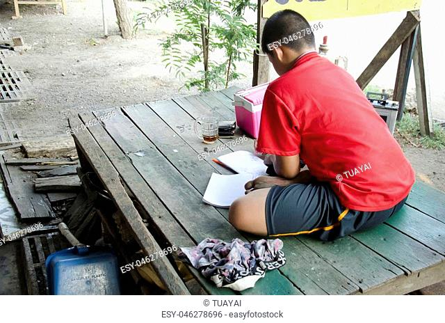 Thai children study and writing homework on notebook at wooden table in house on May 19, 2016 in Samut Sakhon, Thailand