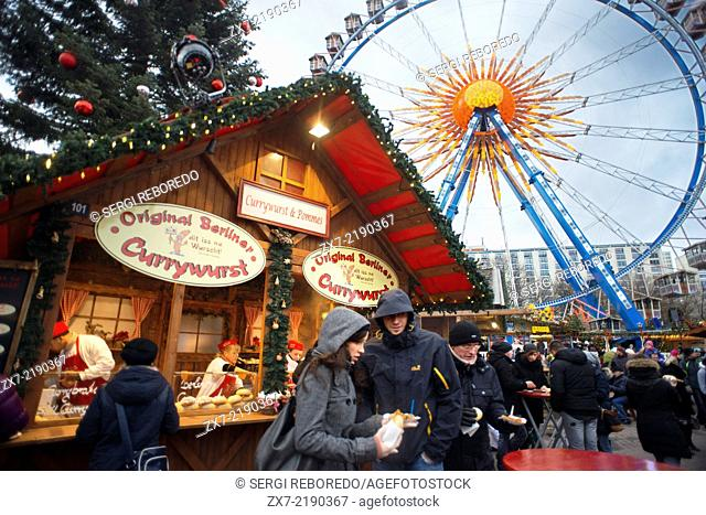 Ferris wheel and currywurst at the Christmas market in front of the Neptunbrunnen fountain, Alexanderplatz, Berlin. Snack Bar at Alexanderplatz
