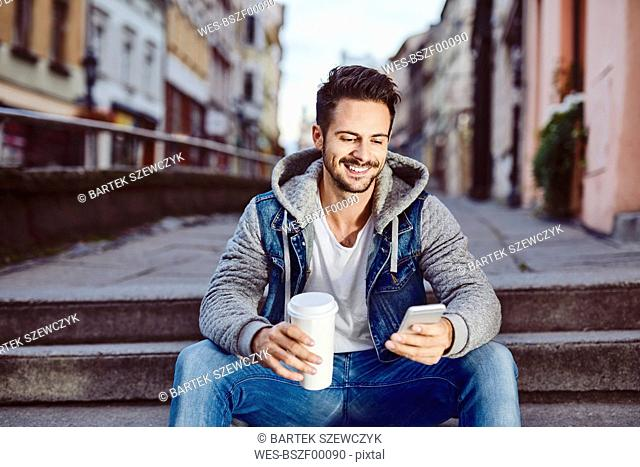 Man with coffee sitting on stairs in the city using phone