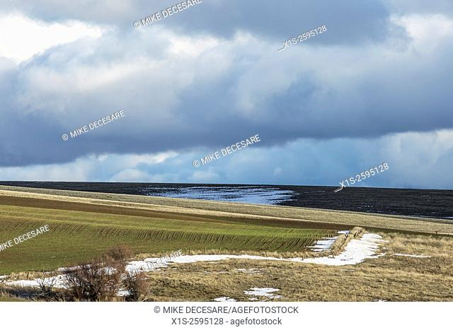 Farm land under dark wintry clouds and scattered snow on the ground