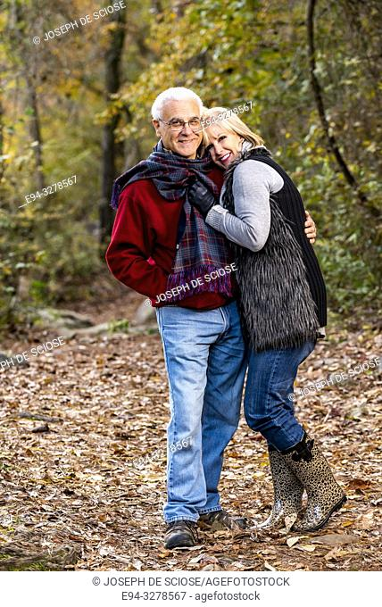 A happy 65 year old man and a 59 year old blond woman hugging in a forest setting looking at the camera