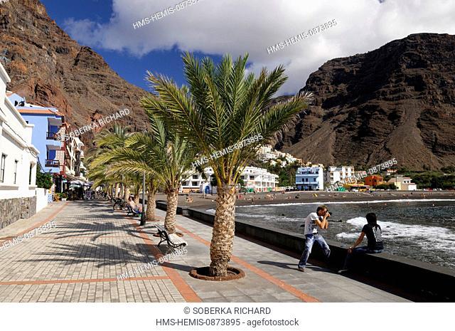 Spain, Canary Islands, La Gomera, Valle Gran Rey, Playa de Calera, tourists taking pictures on the promenade
