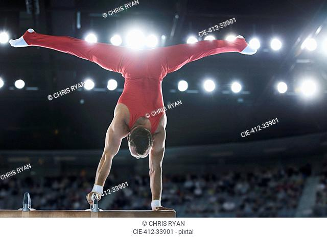 Male gymnast performing upside-down handstand on pommel horse