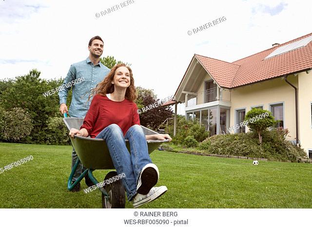 Man pushing smiling woman in wheelbarrow in garden