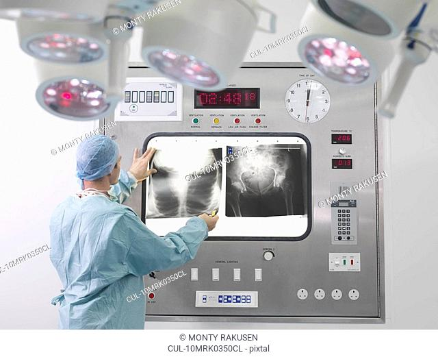 Male surgeon looking at x-rays