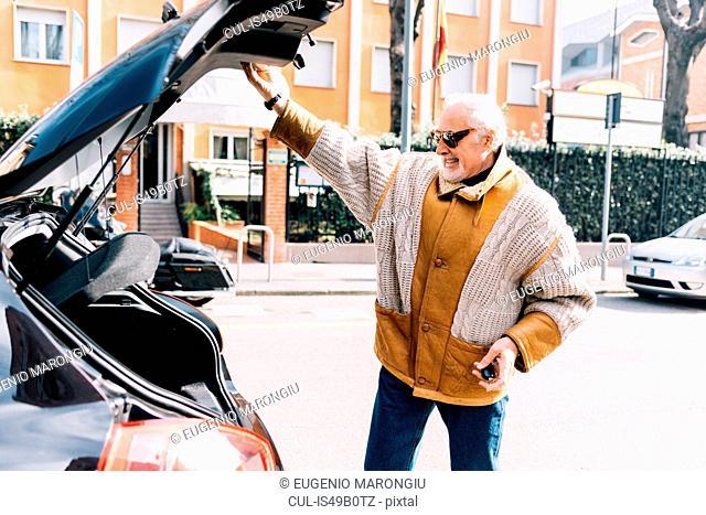 Man holding up car boot door, Milan, Italy