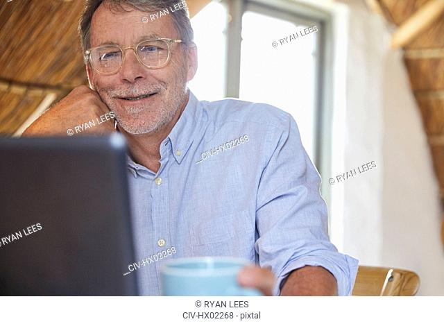 Senior man drinking coffee and using laptop