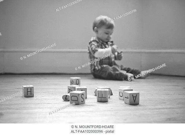 Baby boy playing on floor in nursery
