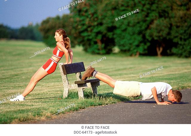young adult woman and Young Adult man do extension practices and waiting time pillar in the park