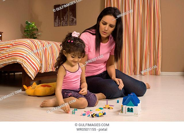 Daughter 3-4 playing toys with mother
