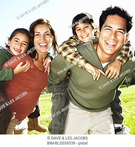 Hispanic family giving piggy back rides in park