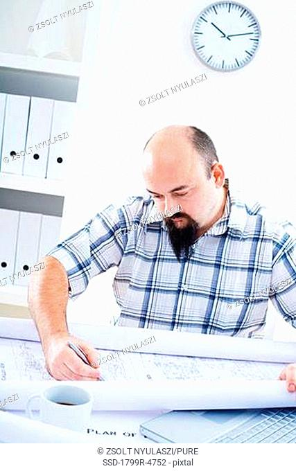 Front view of designer working with blueprints
