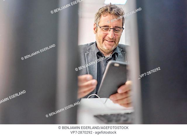 senior business man checking mobile device at work