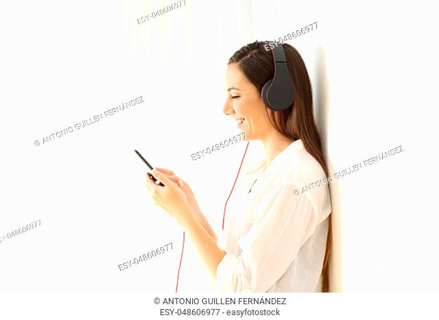 Side view portrait of a happy girl listening music isolated on white at side in a house interior
