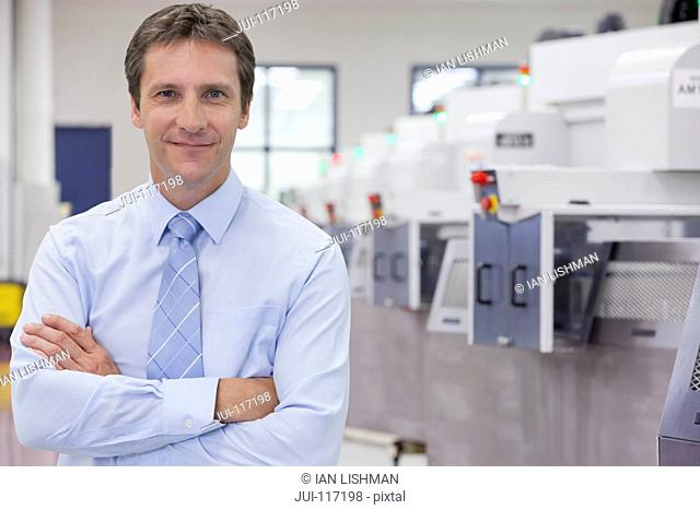 Portrait Of Businessman On Floor Of Engineering Factory