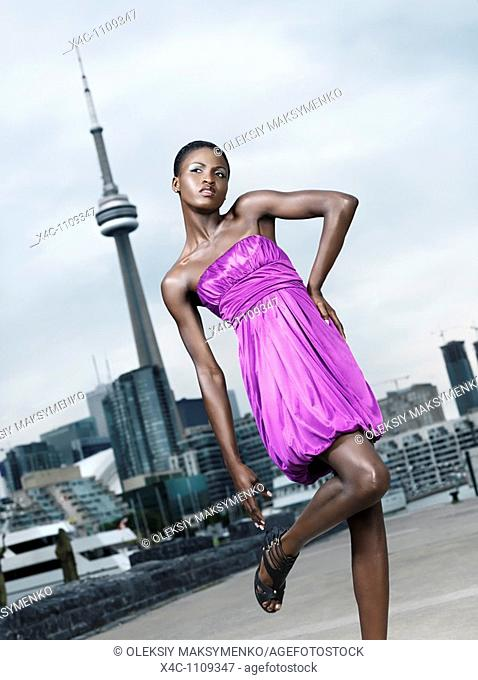 Young woman fashion model posing in front of CN tower in Toronto, Canada