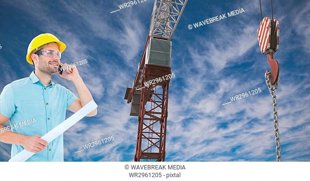 Architect using mobile phone while holding blue print by crane against sky