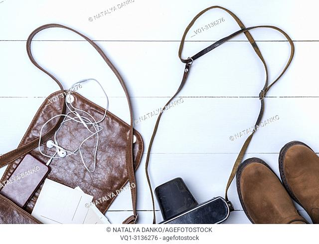 open brown leather bag, boots and vintage camera on a white wooden background, top view