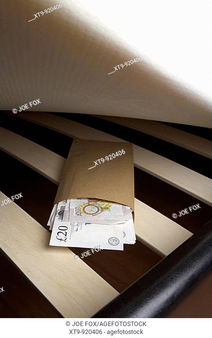 wad of 20 and 10 pounds sterling bank of england cash in an envelope stuffed under the mattress of a bed