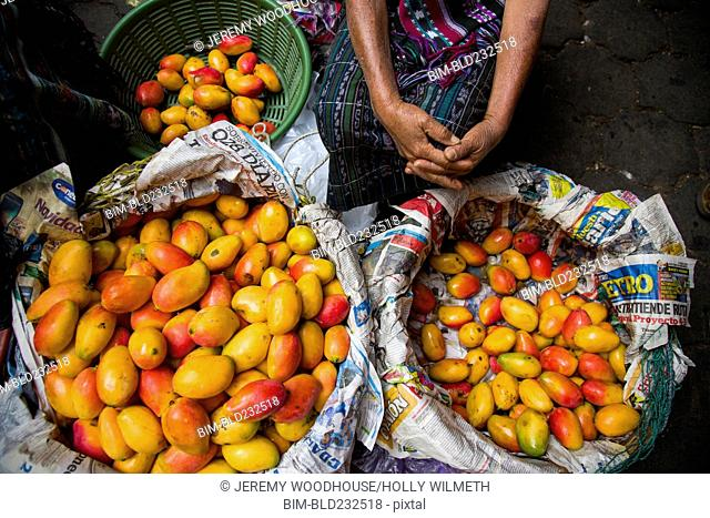 Woman sitting at market with baskets of fresh mangoes