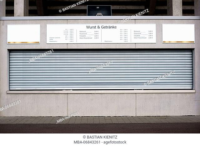 A beer - and sausage stall with let down Venetian blind beyond a football stadium